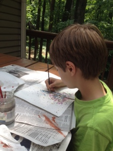 Painting the tree trunk onto the splattered page.